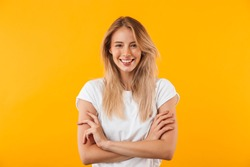 Portrait of a smiling blonde young woman standing with arms folded isolated over yellow background