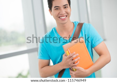 Portrait of a smiling boy with textbooks