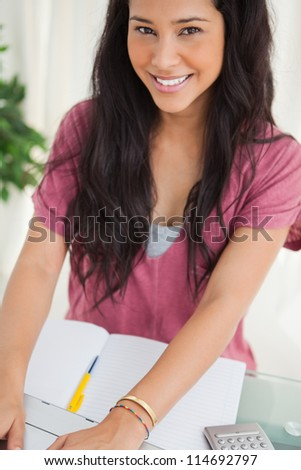 Portrait of a smiling brunette student using a laptop to do her homework