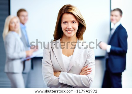 Portrait of a smiling business woman looking at camera with three employees behind