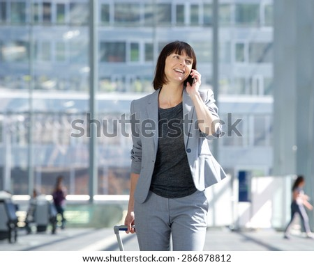 Portrait of a smiling business woman walking and talking with mobile phone at airport
