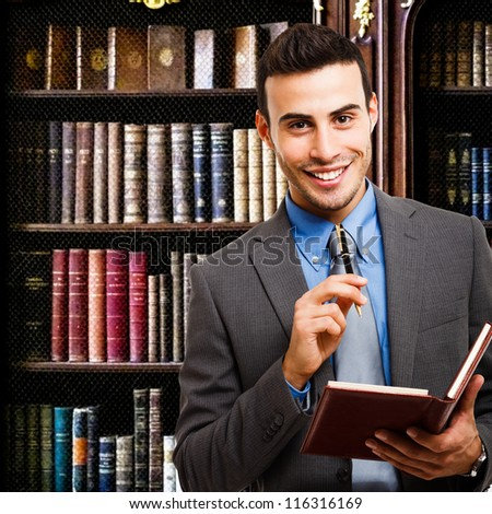 Portrait of a smiling businessman holding an agenda