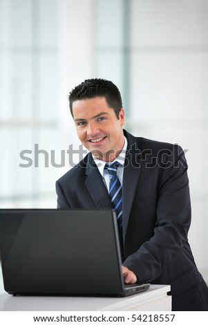 Portrait of a smiling businessman in front of a laptop computer - stock photo