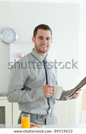 Portrait of a smiling businessman reading the news while having breakfast in his kitchen