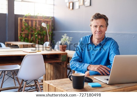 Portrait of a smiling businessman sitting confidently at his desk in a large modern office working online with a laptop
