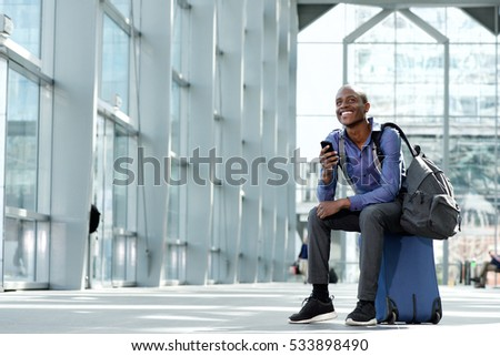 Portrait of a smiling businessman sitting on luggage at airport with cell phone #533898490