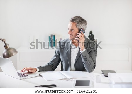 Portrait of a smiling businessman with grey hair and beard talking on his smartphone while he working on his computer while speaking, sitting in his office at his white desk wearing a grey suit.
