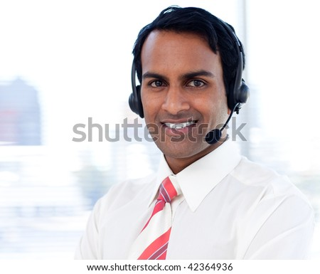 Portrait of a smiling businessman with headsets on in a call centre