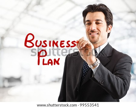"Portrait of a smiling businessman writing ""Business plan"" on the screen"