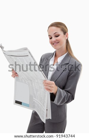 Portrait of a smiling businesswoman reading the news against a white background