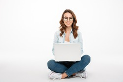 Portrait of a smiling casual girl holding laptop computer while sitting on a floor isolated over white background