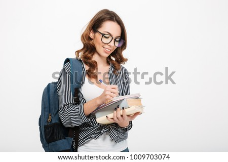 Portrait of a smiling casual girl student with backpack writing in a notepad while standing with books isolated over white background