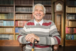 Portrait of a smiling caucasian elderly man sitting in a chair in the library
