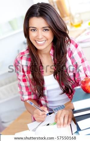 Portrait of a smiling  caucasian teen girl studying  at home