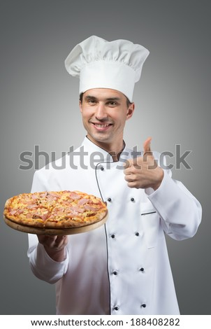 Portrait of a smiling chef showing fresh pizza and thumbs up