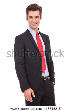 Portrait of a smiling confident business man standing with his hands in the pockets.