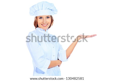 Portrait of a smiling cook woman showing something. Isolated over white background.