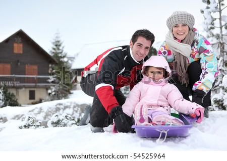 Portrait of a smiling couple and a little girl sledding