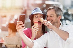 Portrait of a smiling couple eating ice cream and having fun in the city. The grey hair man with a beard is taking a selfie with phone. they make funny faces