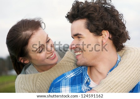 Portrait of a smiling couple hugging outdoors