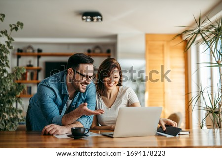 Portrait of a smiling couple looking at laptop together at cozy home office.
