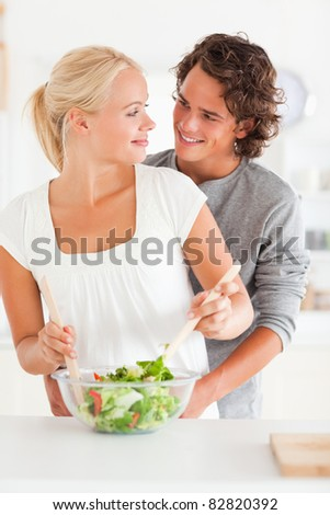 Portrait of a smiling couple preparing a salad in their kitchen
