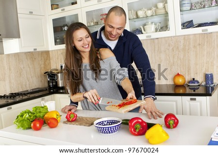 Portrait of a smiling couple preparing food together at home