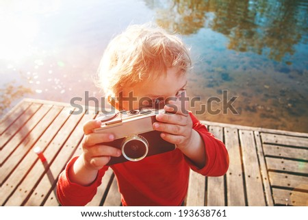 Portrait of a smiling cute boy taking picture with retro camera at a lake