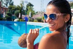 Portrait of a smiling cute woman drinking cocktail in swim pool outdoors