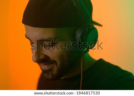 Photo of  Portrait of a smiling disc jockey in the club with pulsating and psychedelic lights. Nightclub and music concept