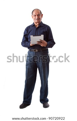 Portrait of a smiling elderly East Indian businessman using a digital tablet stock photo