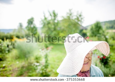 portrait of a smiling elderly lady in the garden #375353668
