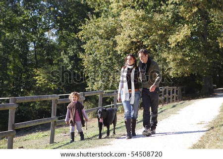 Portrait of a smiling family and a dog in the countryside