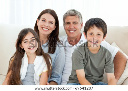 Portrait of a smiling family at home. Focused on children