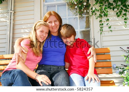 Portrait of a smiling family - mother and children - in front of the house
