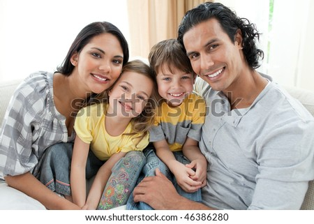 Portrait of a smiling family sitting on sofa at home - stock photo