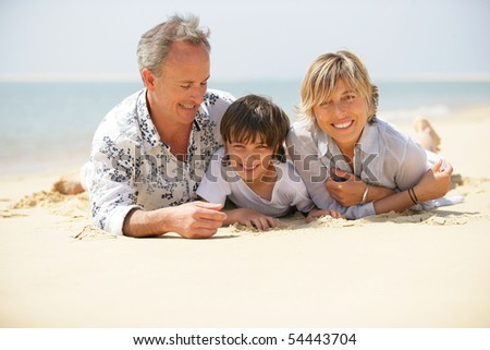 Portrait of a smiling family stretched out in the sand