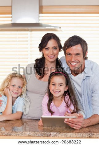 Portrait of a smiling family using a tablet computer together in a kitchen