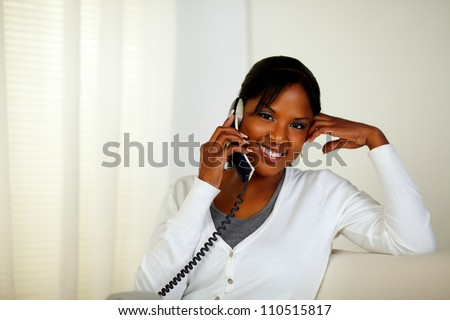 Portrait of a smiling female looking at you while speaking on phone at home indoor