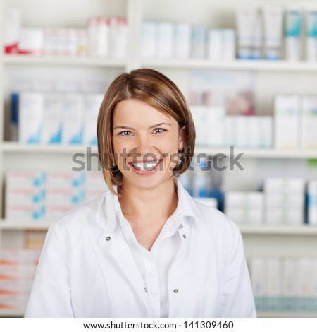Portrait of a smiling female pharmacist with a beautiful big smile standing in her pharmacy
