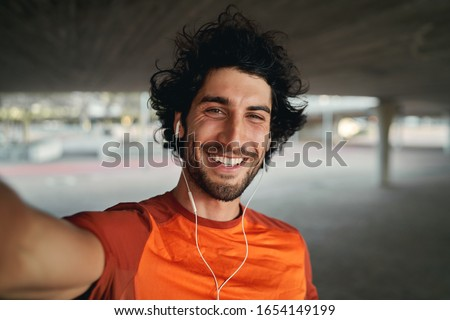 Portrait of a smiling fit young man with earphones in his ears taking selfie outdoors - pov shot of a man looking at the camera smiling taking a selfie