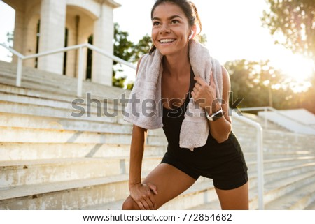 Portrait of a smiling fitness girl with towel resting after work out outdoors #772854682
