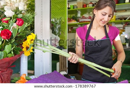 Portrait of a smiling florist business woman owner working at her flower store counter preparing an new floral arrangement cutting the stems of yellow sunflowers. Small business.