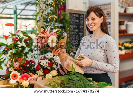 Portrait of a smiling florist making bouquet for a client, standing at counter and looking at camera. Photo stock ©