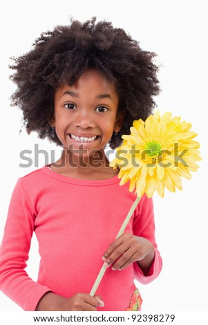 Portrait of a smiling girl holding a flower against a white background