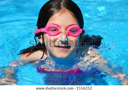 Portrait of a smiling girl in pink goggles in a swimming pool