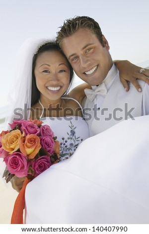 Portrait of a smiling groom carrying a happy bride outdoors