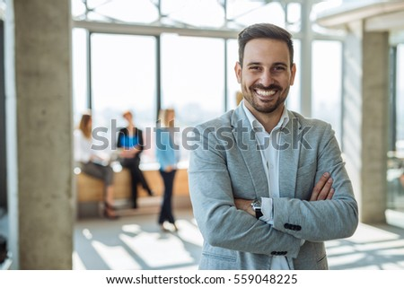 Portrait of a smiling handsome businessman with crossed arms.