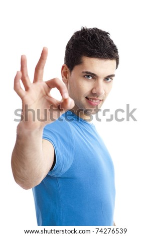 Portrait of a smiling handsome young man gesturing ok sign over a  white background