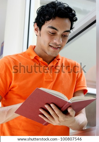 Portrait of a smiling handsome young man reading a book